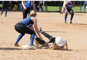 Michael Murray/Americus Times-Recorder:   Lady Raider, Brandi Sellars, dives back to the bag to avoid getting picked off in the first match of the GISA softball quarterfinals in Americus.