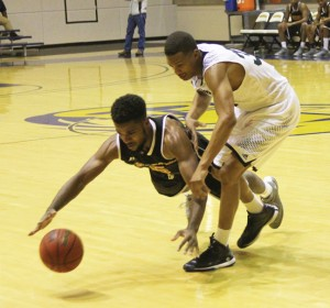 Michael Murray/Americus Times-Recorder:   Damien Leonard and a Tuskegee defender scramble for control of a loose ball during the 'Canes' Dec. 1 match in Americus. The Hurricanes won the match 76-56.