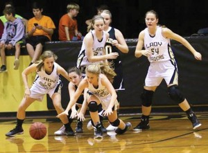 Photo by Sheri Bass:   Sydney Payne (12) and Chris Shattles (22) scramble for control of a loose ball against a Crisp Academy competitor during Southland's Dec. 8 contest in Americus. In the background are, at left, Macy Williaams and Savannah Banks, at right.