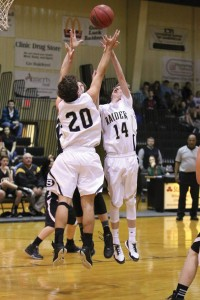 Photo by Sheri Bass:   Landon Henson and (20) and Ridge Roland (14) jump for a rebound on Dec. 8 as the Raiders take the win over Crisp Academy.
