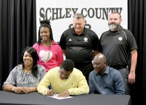 Michael Murray/Americus Times-Recorder:   This photo, from the April 10, 2015 edition of the Times-Recorder, shows Schley County running back, Tra Minter, signing a national letter of intent to play football for Garden City Community College during the 2015-16 season. Shown with Minter are his family members and members of the Schley County Wildcats' coaching staff.