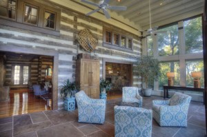 The atrium offers a more panoramic view of the vista behind the historic log house.