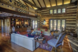 The great room of Sally Run offers an inviting interior with windows overlooking the lush landscape behind the house.
