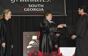South Georgia Technical College Acting President Janice Davis, center, is shown presenting Moises Duarte with his associate of applied science agricultural technology degree. TCSG Commissioner Gretchen Corbin, at left, is also shown waiting to congratulate Duarte.