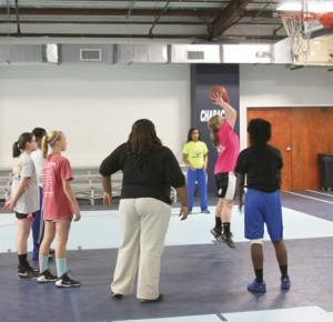 Michael Murray/Americus Times-Recorder: Lady Panther assistant coach, Tiera Wallace and players, Tykiera Long (rear) and Timia Swanson (front) teach shooting drills to members of the SCPRD 11-12 year-old girls basketball team.