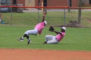 Michael Murray/Americus Times-Recorder:   ASHS second-baseman, Kendall Butler (left), tumbles backwards after making a leaping catch to dispatch a Monroe runner on a pop fly during the April 11 contest. ASHS right fielder, Jamorrian Johnson (right), provides back-up.