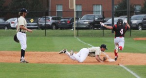 Michael Murray/Americus Times-Recorder:   GSW pitcher, Matt Hubbard, makes a diving tag  at first base to dispatch a VSU runner during the sixth inning of the Hurricanes' March 30 match against the Blazers. First baseman, Davey King (left), made the toss to Hubbard after fielding the ball.