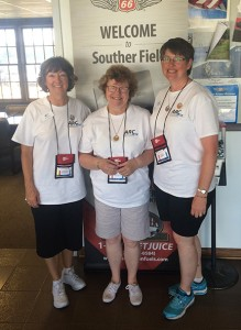 """Michael Murray/Americus Times-Recorder:   From left; Donna Harris, Joanne Allcorn, and Lara Gaerte, pause for a photo op in front of the """"Welcome To Southerfield"""" sign, located at the Jimmy Carter Regional Airport in Americus. The trio of pilots, who have been working together on the director's board of the ARC for years, flew the race together this year."""