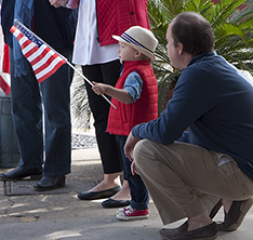 Henry Hart V shows that it's never too early to be patriotic. His father, Hank Hart, is shown kneeling beside him.