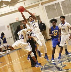 MICHAEL MURRAY I ATR:   ASHS' Eric Hall (11) and Karmil Hamilton (10) leap after the ball following the tip-off of the Panthers' contest against the Crisp County Cougars on Dec. 9 in Americus. Hall led the Panthers to victory with 18 points scored in the contest.