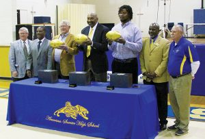 MICHAEL MURRAY I ATR:   In this photo, from the Feb. 20, 2016 edition of the Tiimes-Recorder, former NFL players (holding footballs from left) Dan Reeves, Kent Hill, and Leonard Pope, are shown with members of the Sumter County School System staff after presenting the awards to the school for its role in producing three Super Bowl participants.