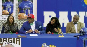 MICHAEL MURRAY I ATR:   ASHS defensive tackle, Tyler Clark, prepares to sign on with the University of Georgia Bulldogs in this photo from the Feb. 6, 2016 edition of the Americus Times-Recorder. Seated with Clark are family members.