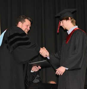 Austin Crook of Smithville earned his associate of applied science degree in agricultural technology. President Watford is shown presenting his diploma.