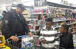 Americus Police Sgt. Eddie Davis talks with two of the kids about what they want to put in the shopping cart next.