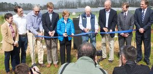 Former President Jimmy Carter and his wife Rosalynn, at center, participated Wednesday in the ribbon cutting of the SolAmerica solar energy project on the Carters' farm. S
