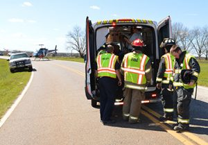 Personnel with Sumter County Fire & Rescue load one of the accident victims into a Gold Star ambulance for transport to Phoebe Sumter Medical Center, while an Air Evac helicopter in the background awaits another victim for transport to a Macon hospital.